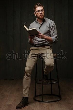 Jovem barbudo homem óculos sessão leitura Foto stock © deandrobot