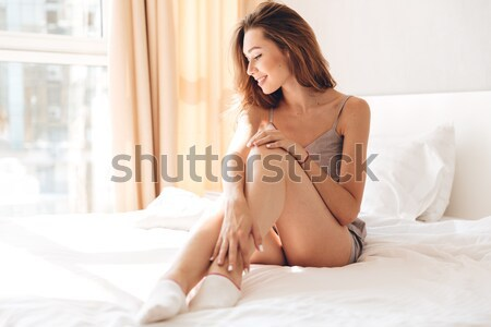 Desperate hopeless young woman sitting on bed Stock photo © deandrobot