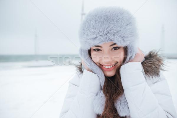 Happy young woman wearing hat walking near beach Stock photo © deandrobot