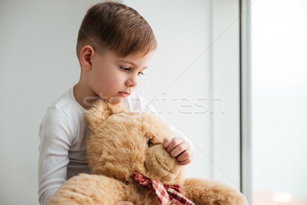 Sad boy near window with teddy bear waiting for parents Stock photo © deandrobot