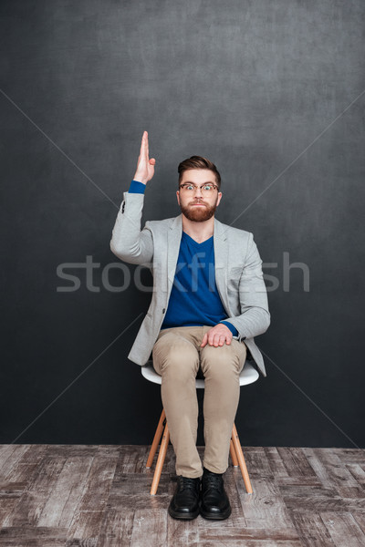 Amusing young man geek in glasses sitting with raised hand Stock photo © deandrobot