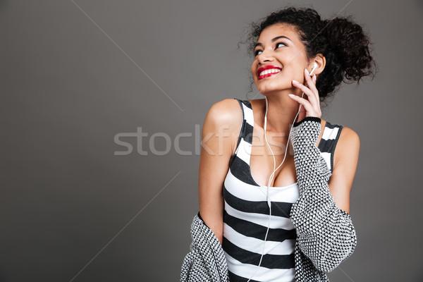 Nevet afro amerikai nő mobiltelefon fülhallgató Stock fotó © deandrobot
