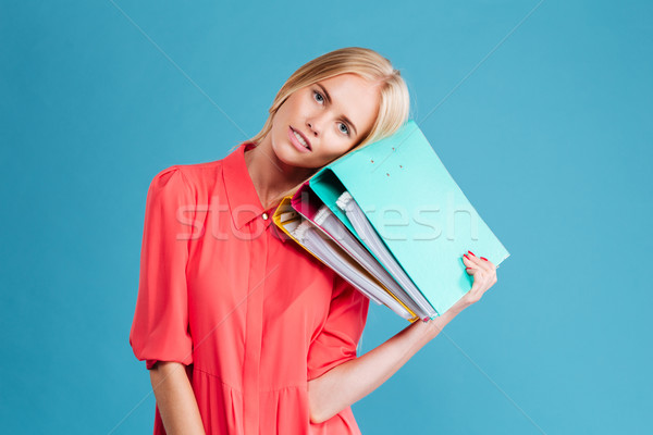 Exhausted young blonde woman with her head on folders Stock photo © deandrobot