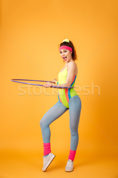Cheerful young fitness woman working out and using hula hoop Stock photo © deandrobot