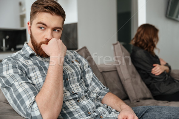 Young sad quarrel loving couple sitting on sofa indoors. Stock photo © deandrobot