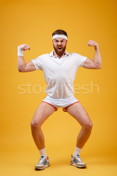 Vertical image of screaming sportsman showing biceps Stock photo © deandrobot