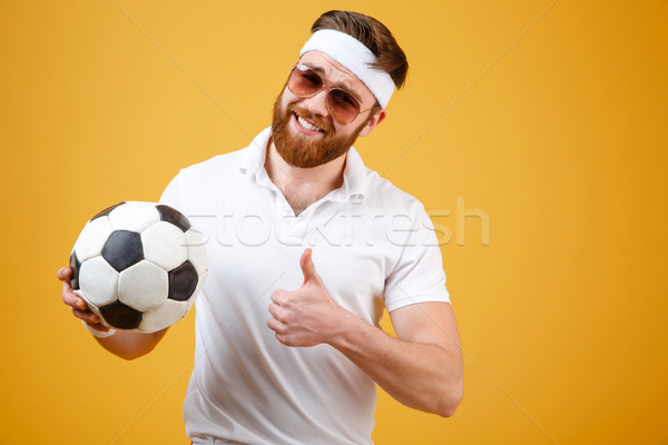 Smiling sportsman holding soccer ball and showing thumb up Stock photo © deandrobot