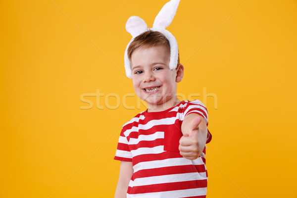Cheerful little boy wearing rabbit ears and showing thumbs up Stock photo © deandrobot