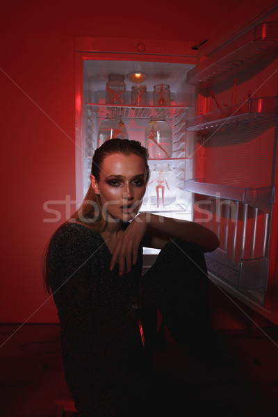 Vertical image of unusual woman sitting near the fridge Stock photo © deandrobot