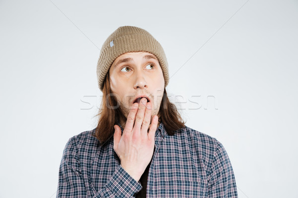 Shocked hipster covering his mouth and looking away Stock photo © deandrobot