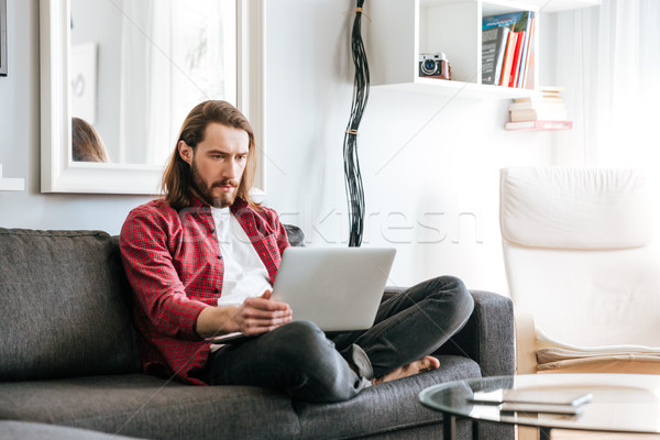 Serious man sitting and using laptop on sofa at home Stock photo © deandrobot