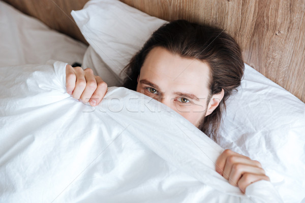 Handsome man hiding his face under white coverlet in bed Stock photo © deandrobot
