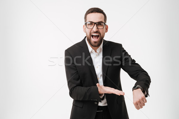 Screaming young bearded businessman showing his watch. Stock photo © deandrobot