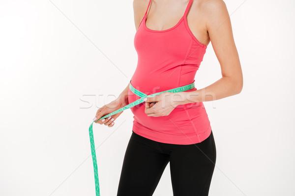 Kép terhes fitnessz nő mérés pocak fehér Stock fotó © deandrobot
