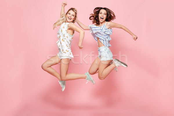 Two cheerful excited young women jumping and having fun together Stock photo © deandrobot