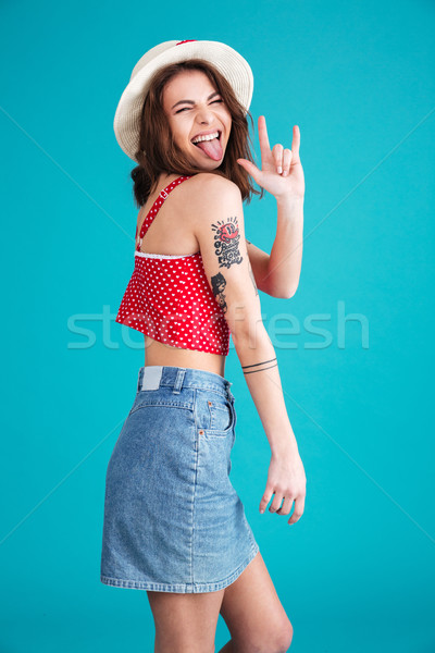 Funny naughty girl in hat showing rock sign with fingers Stock photo © deandrobot