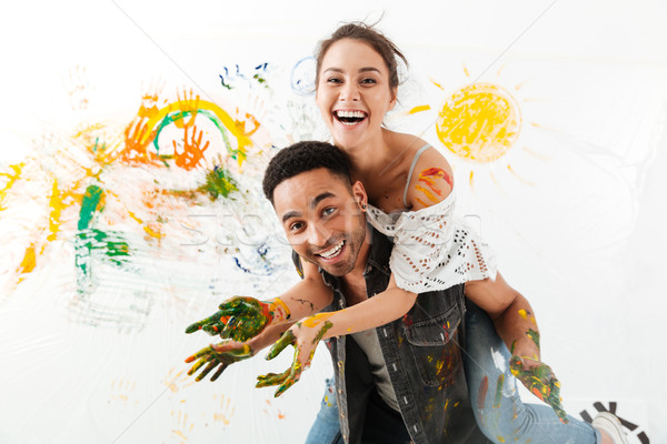 Stock photo: Man with hands dirty in paints holding girlfriend on back