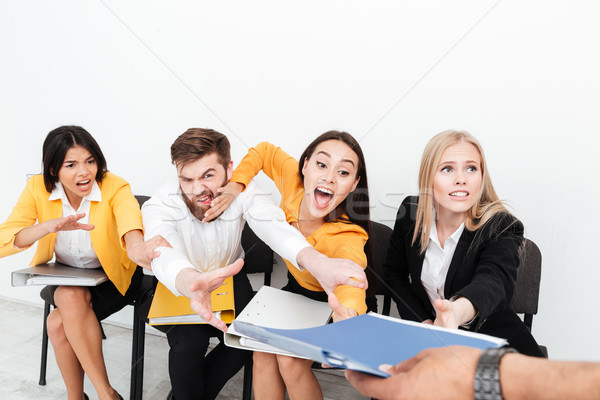 Emotional colleagues sitting in office tries to get folder. Stock photo © deandrobot