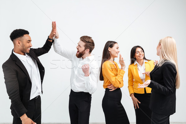 Smiling colleagues business team standing in office gives a high-five Stock photo © deandrobot
