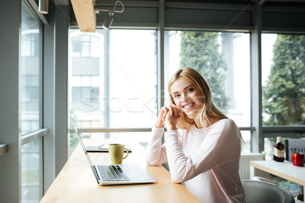 Happy lady sitting in office coworking while using laptop Stock photo © deandrobot