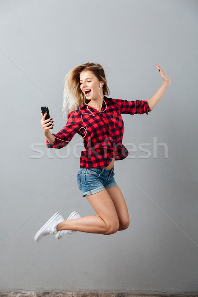 Happy young blonde woman jumping listening music by phone. Stock photo © deandrobot