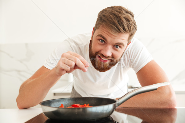 Happy bearded man sprinkle with condiments of vegetables Stock photo © deandrobot