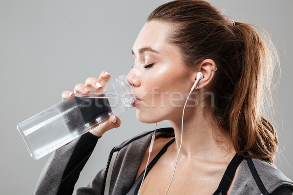 Close up picture of sports woman drinking water Stock photo © deandrobot