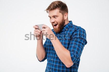 Barbu homme à carreaux shirt hurlant smartphone Photo stock © deandrobot