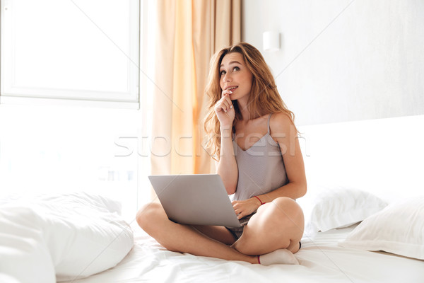 Happy emotional lady sitting on bed indoors chatting by laptop. Stock photo © deandrobot