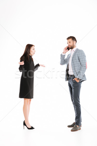 Angry woman looking at man talking by phone Stock photo © deandrobot