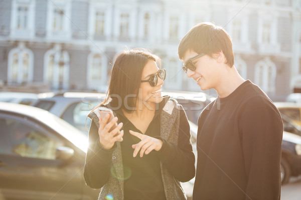 Cheerful young woman walking outdoors with brother using phone. Stock photo © deandrobot