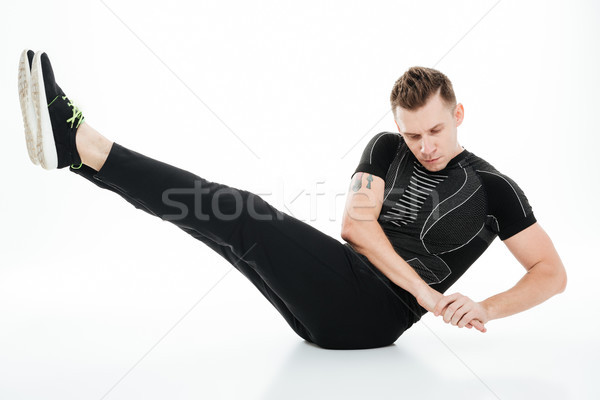 Young concentrated sportsman doing abdominal exercises on the floor Stock photo © deandrobot