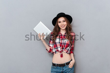 Smiling woman in plaid shirt standing and working on laptop Stock photo © deandrobot