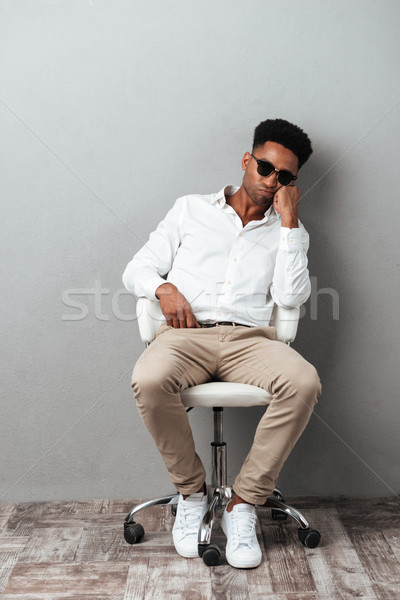 Tired afro american man in sunglasses sitting in a chair Stock photo © deandrobot