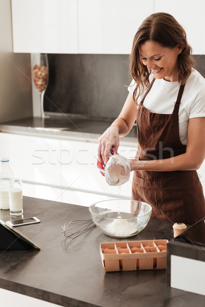 Vertical image of smiling casual woman cooking near the table Stock photo © deandrobot