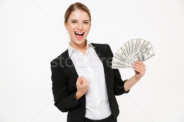 Happy screaming blonde business woman holding money Stock photo © deandrobot