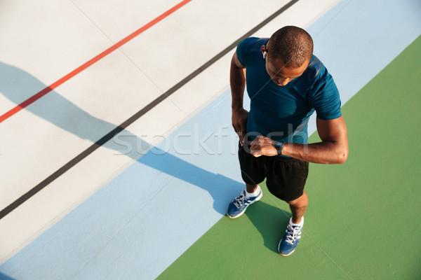 Top Ansicht african Sportler schauen Armbanduhr Stock foto © deandrobot