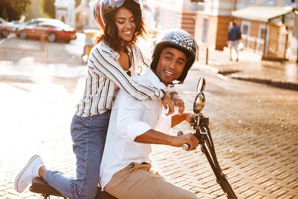 Vista lateral satisfeito africano casal moderno motocicleta Foto stock © deandrobot