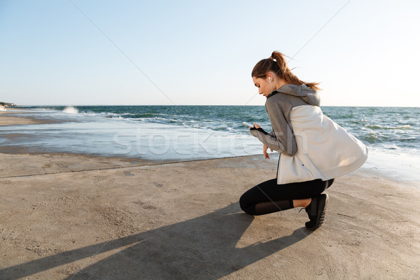 Back view of young sport woman sitting on knee, looking at smart Stock photo © deandrobot