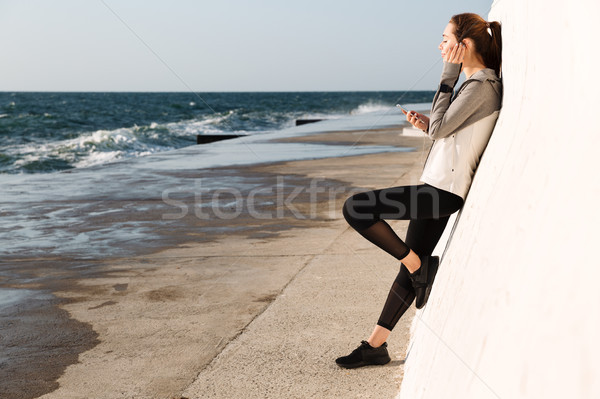 Full-length photo of young healthy sport woman, listening to mus Stock photo © deandrobot