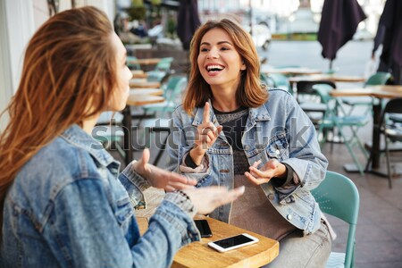 Stock photo: Two pretty brunette woman in keans casual wear having fun while