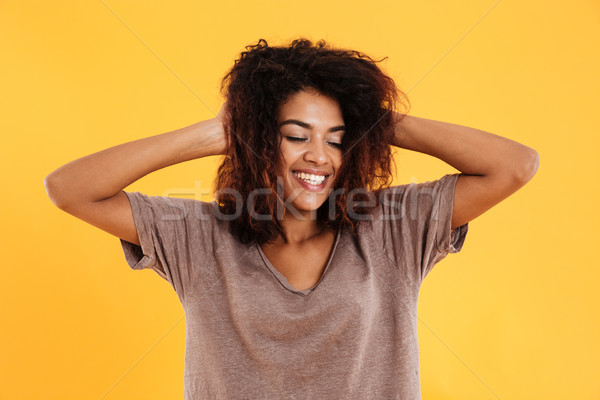 Happy african woman posing with closed eyes and holding head Stock photo © deandrobot
