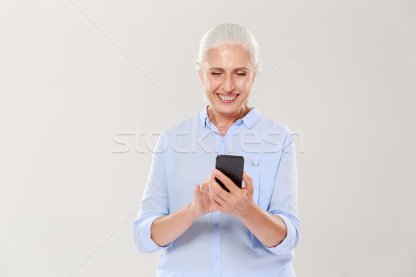 Mature smiling woman using smartphone isolated Stock photo © deandrobot
