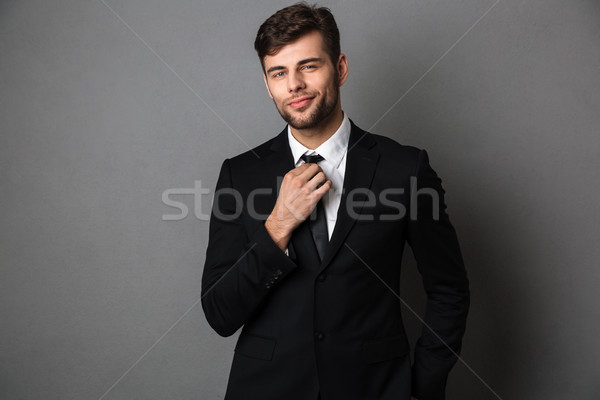 Young attractive man in classic suit straightens his tie, lookin Stock photo © deandrobot