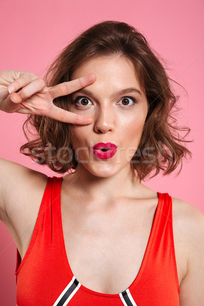 Close-up portrait of beautiful young woman with red lips showing Stock photo © deandrobot