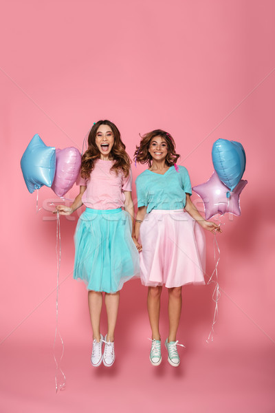 Full length portrait of two happy girls with balloons holding ha Stock photo © deandrobot