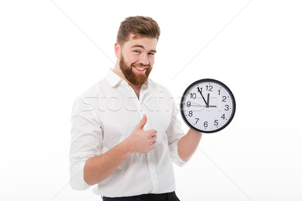 Pleased bearded man in business clothes holding clock Stock photo © deandrobot