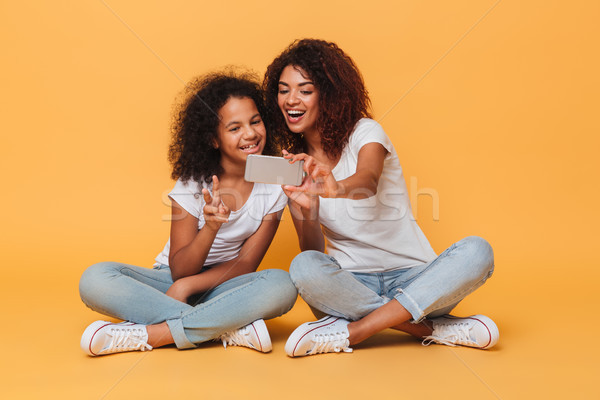Portrait of a two joyful afro american sisters Stock photo © deandrobot
