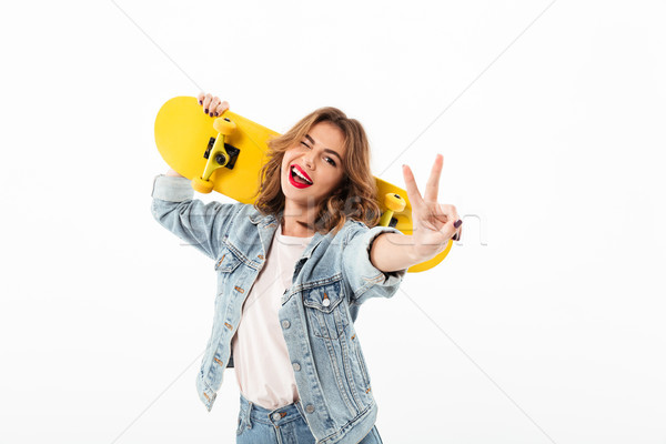 Happy woman in denim clothes with skateboard having fun Stock photo © deandrobot