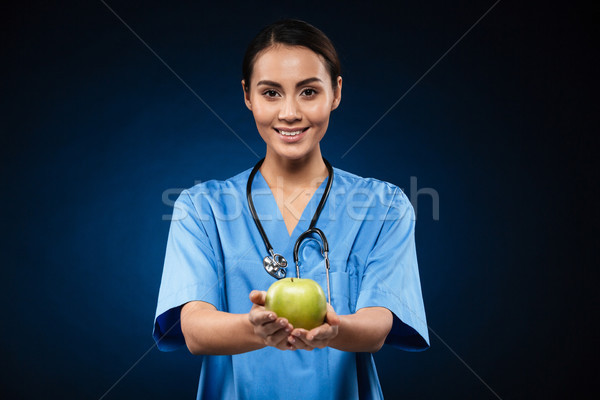 Happy healthy doctor holding green apple isolated Stock photo © deandrobot